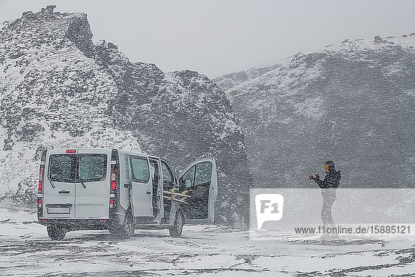 A person standing in a snowy wintry landscape taking a photograph of a campervan. Winter Surfing