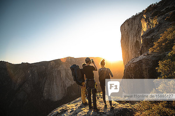 Eine Gruppe von Menschen steht auf einem Felsen und fotografiert einen Sonnenuntergang.