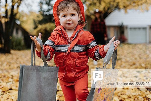 Ein Kind  das zu Halloween als Feuerwehrmann verkleidet ist  geht durch einen Park mit Blättern auf dem Boden.