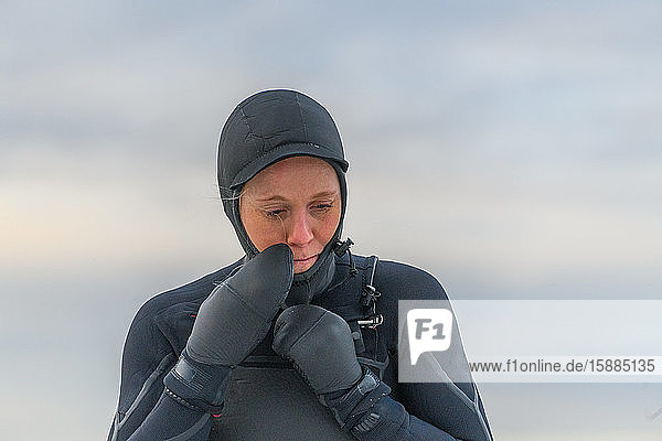 Head and shoulders close up of a woman wearing a full wetsuit.