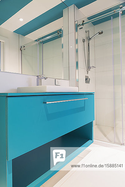 Interior view of modern bathroom with white floor tiles and walls  glass shower screen and wall mirror over bright blue vanity unit.