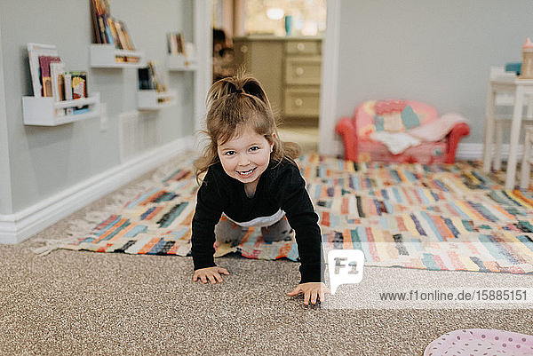 A young girl crawling towards the camera and smiling.
