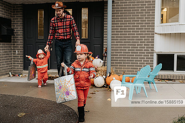 Two children dressed as firefighters walking away from the front door of a house decorated for Halloween with their father.
