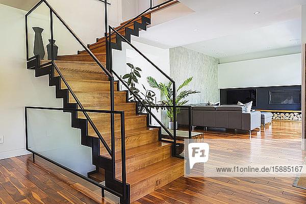 Wohnzimmer mit grauem Sofa und Ottomane auf Holzboden  Holztreppe mit Metallhandläufen.