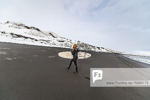 Eine Frau  die ein Surfbrett trägt  geht über einen schwarzen Strand mit Schneehügeln im Hintergrund.