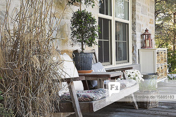 Outdoor deck with wooden chairs  plant pots with plants and honey coloured stone house.