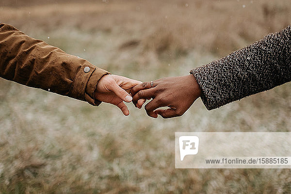 Interracial couple  man and woman holding hands  one wearing a gold wedding ring.
