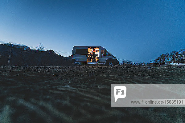 Campervan silhouetted on a hill in the evening with the lights on inside and a man standing by the open side door.
