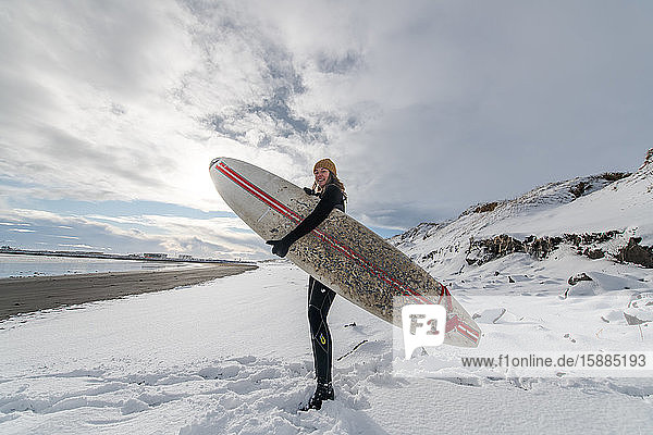 A woman wearing a wetsuit and holding a surfboard standing on a snowy beach and looking out to sea.
