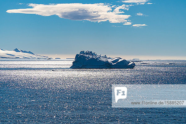 An iceberg floating in the Southern Atlantic Ocean below a blue sky with a cloud.