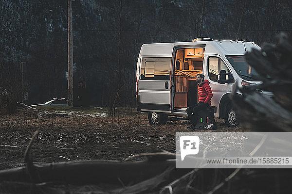 Ein Mann sitzt abends vor seinem Wohnmobil mit dem Wald im Hintergrund.