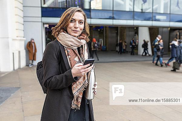 Porträt einer Frau mit Mobiltelefon vor dem Bahnhof  London  UK