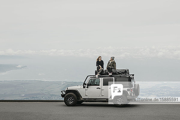 Friends talking while sitting on top of SUV at Maui  Hawaii  USA