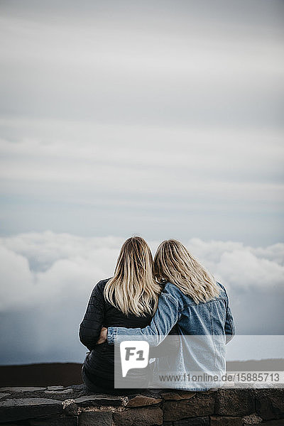 Rear view of female friends looking at idyllic cloudscape while sitting at Haleakala Volcano  Hawaii  Maui  USA