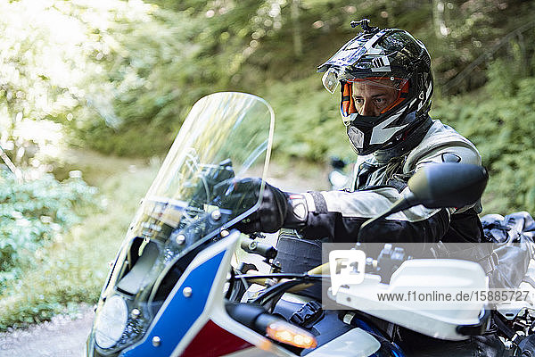 Motorradfahrer auf einer Reise beim Einstellen des Navigationssystems Motorradfahrer auf einer Reise beim Einstellen des Navigationssystems