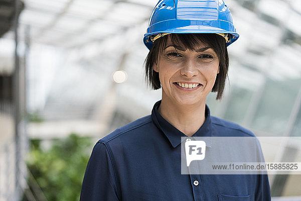 Architektin mit blauem Schutzhelm  Porträt