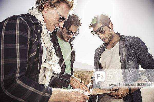 Drei Männer mit Karte auf dem Land