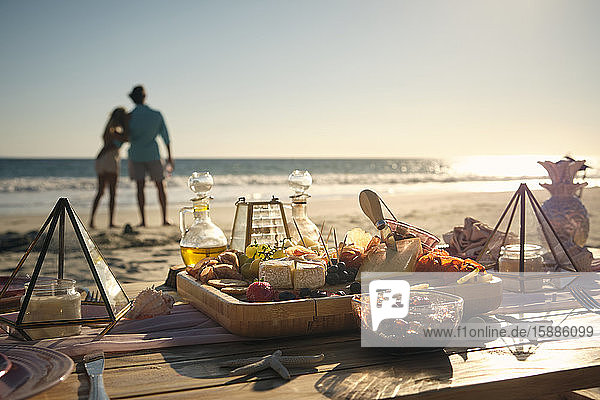 Fresh food on dining table with mature couple looking at sea during sunny day  Riviera Nayarit  Mexico