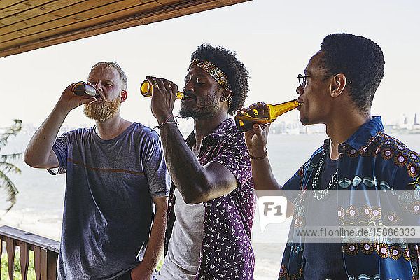 Male friends drinking beer while standing in balcony