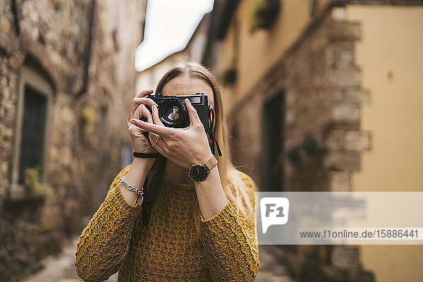Young woman taking a picture with old-fashioned camera in old town  Greve in Chianti  Tuscany  Italy
