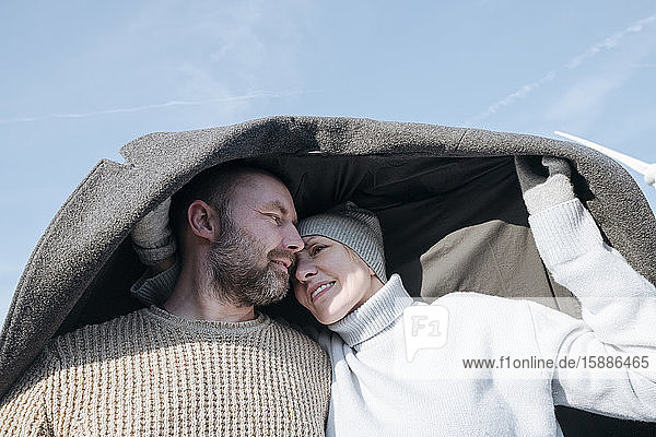 Porträt eines reifen Paares  das sich unter dem Mantel versteckt