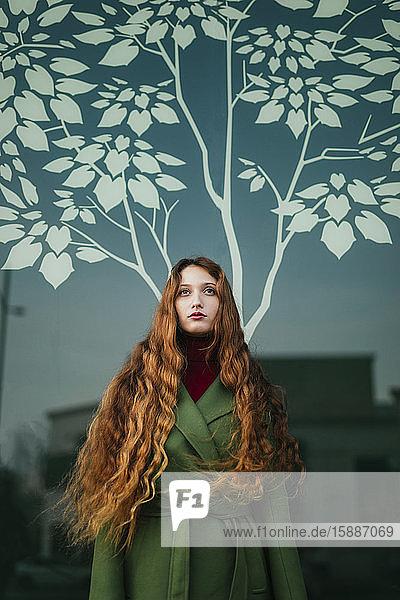 Porträt einer rothaarigen jungen Frau mit wehendem Haar  die nach oben schaut