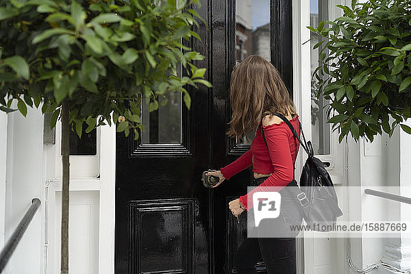 Junge Frau öffnet Haustür Junge Frau öffnet Haustür