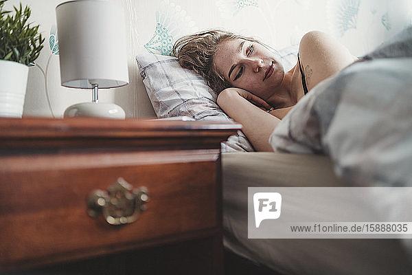 Attraktive junge Frau  die zu Hause im Bett liegt Attraktive junge Frau, die zu Hause im Bett liegt