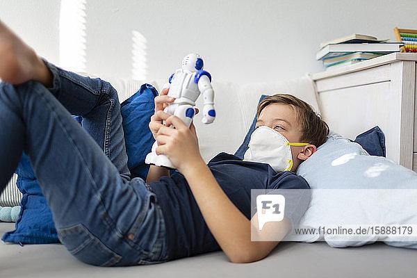 Junge mit Maske spielt während der Koronakrise mit seinem neuen  einzigen Freund  einem Roboter  in seinem Zimmer