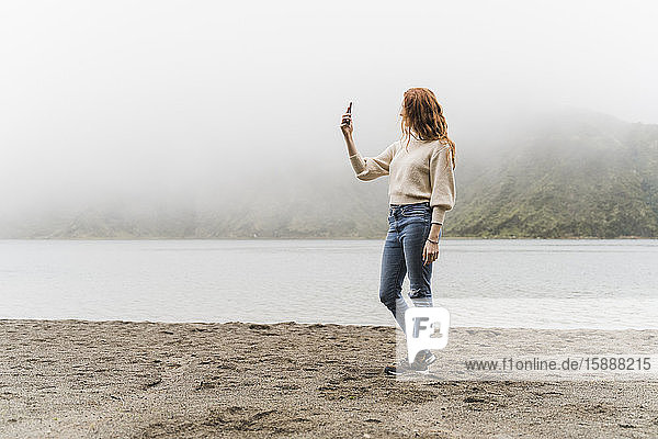 Woman photographing at lakeshore while exploring Sao Miguel Island  Azores  Portugal