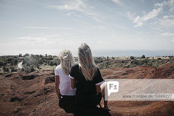 Rückansicht von Freundinnen  die auf der Landschaft im Waimea Canyon State Park sitzen  Kauai  Hawaii  USA