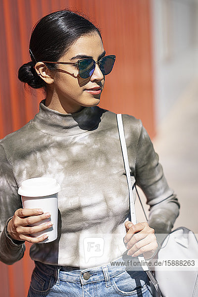 Fashionable young woman holding coffee cup while looking away on sunny day