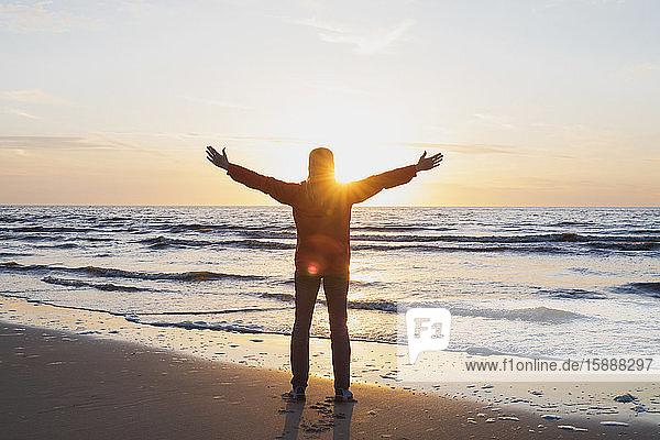 Rückansicht in voller Länge einer Frau mit ausgestreckten Armen  die am Ufer steht  während sie bei Sonnenuntergang das Meer gegen den Himmel betrachtet  Nordseeküste  Flandern  Belgien