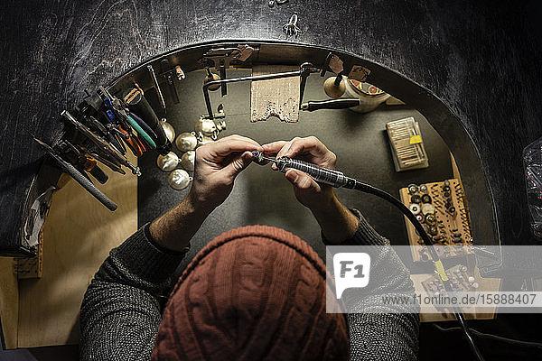 Goldschmied bei der Arbeit am Ring in seiner Werkstatt  von oben Goldschmied bei der Arbeit am Ring in seiner Werkstatt, von oben