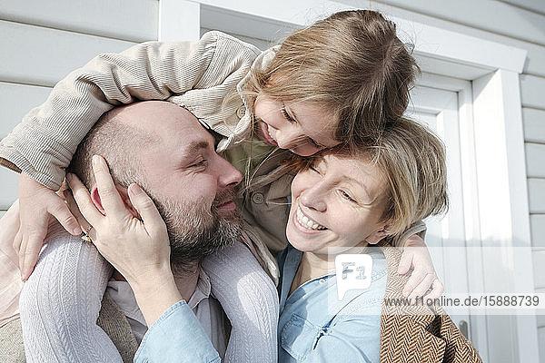 Glückliche Familie  die sich vor ihrem Haus umarmt
