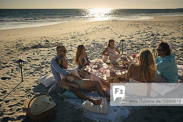 Family and friends enjoying picnic while sitting at beach during sunset. Riviera Nayarit  Mexico