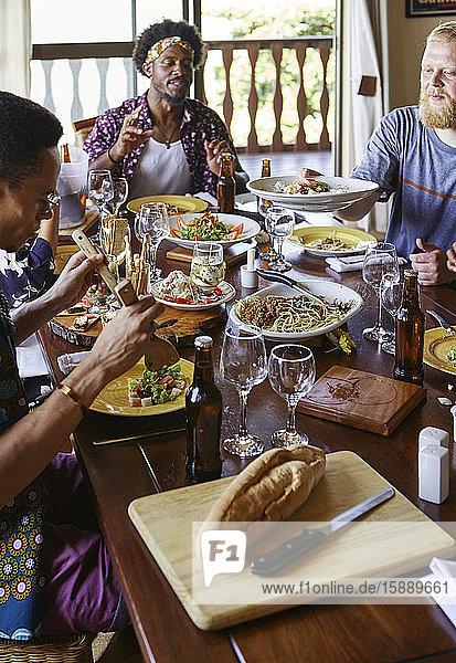 Multiethnische Freunde essen zu Mittag  während sie am Esstisch im Raum sitzen