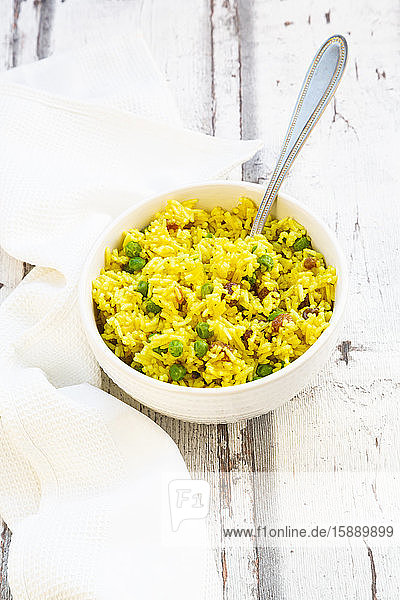 Bowl of pilau rice with green peas  raisins and turmeric