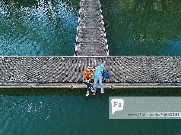 Zwei glückliche Freunde sitzen Seite an Seite auf dem Bootssteg  Valdemurio-Stausee  Asturien  Spanien