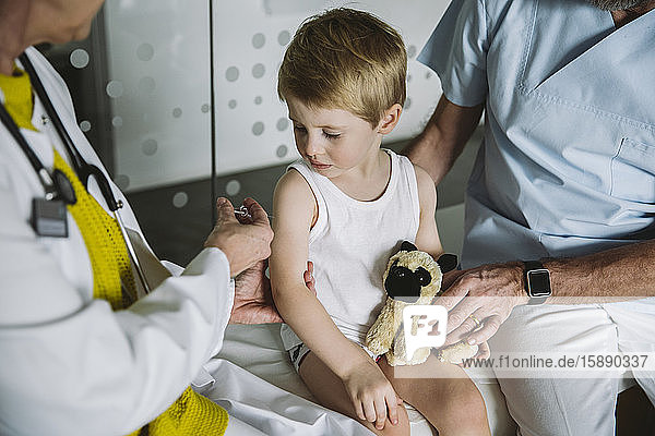 Pediatrist injecting vaccine into arm of toddler
