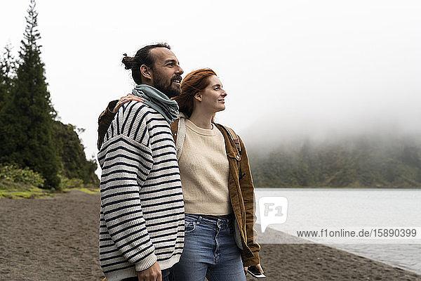 Ein lächelndes Paar betrachtet einen malerischen See  während es Urlaub auf der Insel Sao Miguel  Azoren  Portugal  macht