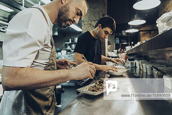 chefs in restaurant arranging food on plates for serving
