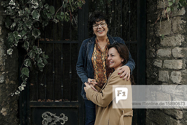 Glückliche Mutter und ihre erwachsene Tochter halten im Freien Händchen