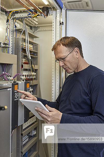 Elektriker mit Tabletteneinstellschaltung am Anschlusskasten Elektriker mit Tabletteneinstellschaltung am Anschlusskasten