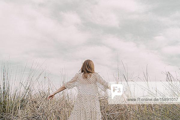 Rückansicht einer Frau in Vintage-Kleid mit ausgestreckten Armen auf einem abgelegenen Feld auf dem Land