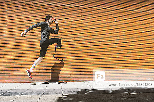 Disabled athlete with leg prosthesis exercising in the city jumping on pavenemt