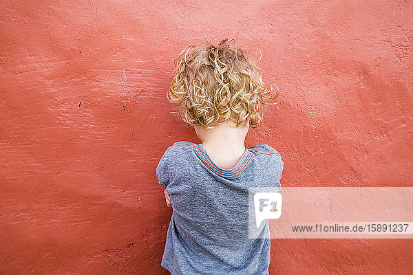 Back view of little boy standing in front of red wall