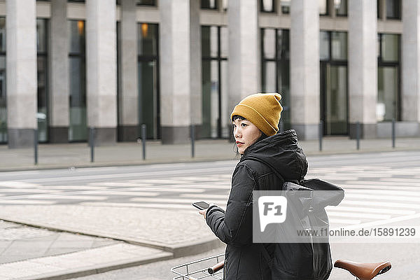 Woman with bicycle and smartphone in the city  Frankfurt  Germany