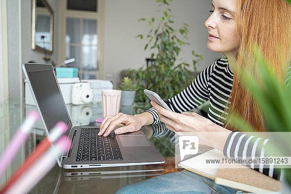 Junge Frau benutzt Laptop und Smartphone am Schreibtisch zu Hause