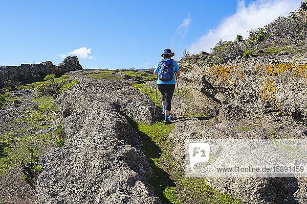 Spanien  Provinz Santa Cruz de Tenerife  San Sebastian de La Gomera  Rückansicht eines älteren Rucksacktouristen  der auf einem felsigen Pfad wandert
